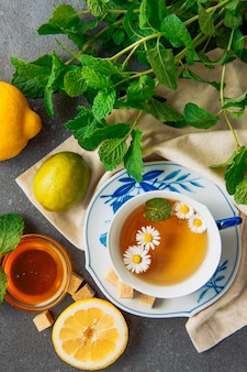 Cup of chamomile tea in a saucer with lemons, brown sugar cubes, honey in glass bowl and green leaves flat lay on a grey and piece of cloth background
