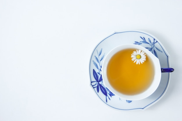 A cup of chamomile tea on a white table. top view.