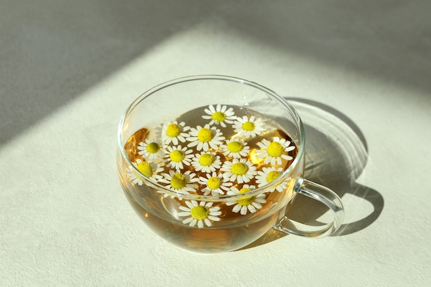 Cup of chamomile tea on white textured table