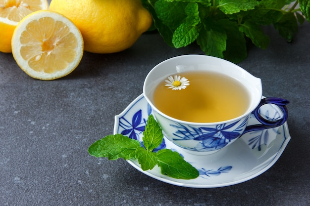A cup of chamomile tea with mint leaves, lemon, high angle view.