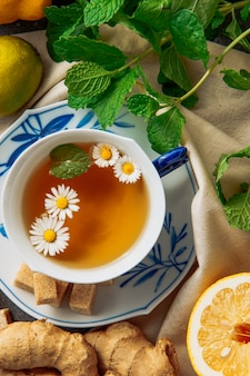 Cup of chamomile tea with sliced lemon, ginger, brown sugar cubes and green leaves in a saucer on piece of cloth background, high angle view.