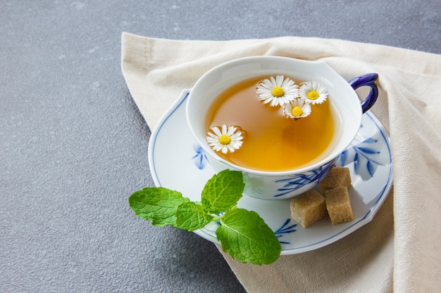 A cup of chamomile tea with sugar cubes, leaves high angle view on a cloth