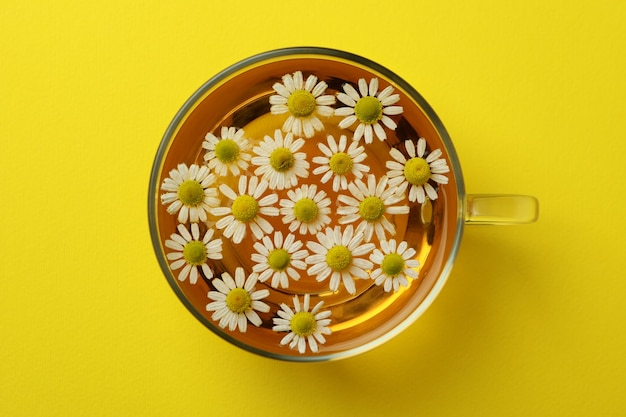 Cup of chamomile tea on yellow