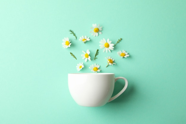 Cup and chamomiles on mint. chamomile tea