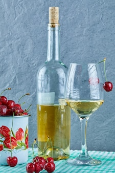 Cup of cherries, bottle of white wine and glass on blue surface