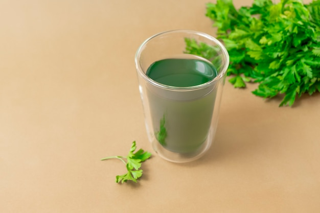 Cup of chlorophyll water on light beige background with copy space