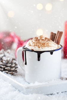 Cup of chocolate with cream and two cinnamon sticks