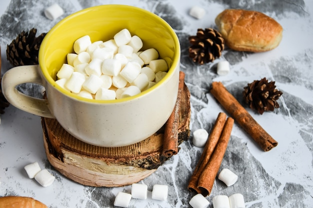 A cup of christmas new year delicious hot chocolate and cocoa with marshmallows sprinkled with cocoa...