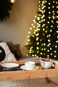 A cup of cinnamon and a saucer on a small makeshift table against a highly blurred background of a christmas tree with garlands