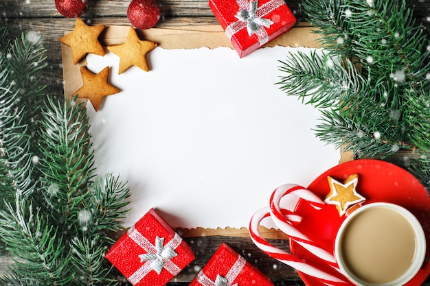 Cup cocoa, cookies, gifts and fir-tree branches on a wooden table
