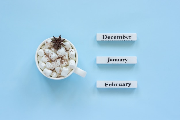 Cup of cocoa marshmallows and calendar december january february on blue background