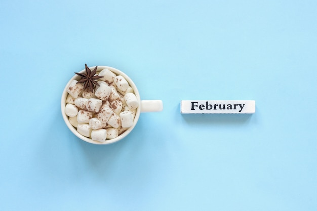 Cup of cocoa marshmallows and calendar february on blue background