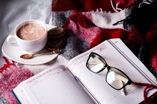 Cup of cocoa staying on open book