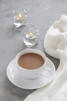 Cup of cocoa on a table, candles and knited blanket.