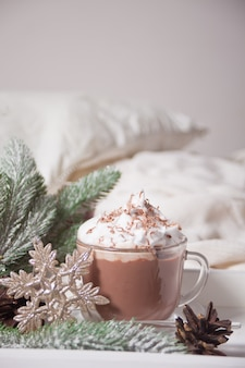 Cup of cocoa on white tray on bed early winter morning