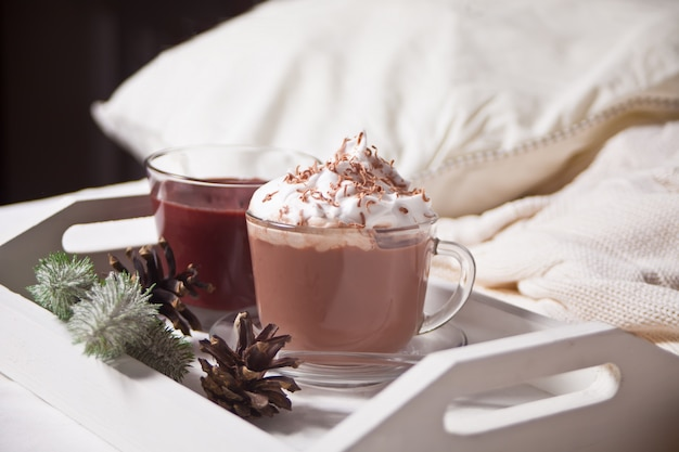Cup of cocoa on the white tray on the bed early winter morning