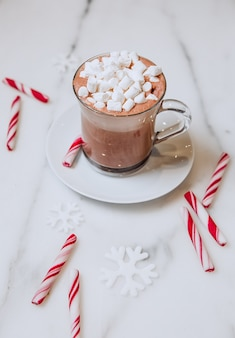 Cup of cocoa with marshmallows and candy striped lollipops on a white background