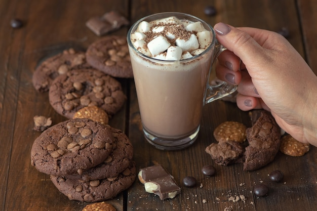 Cup of cocoa with marshmallows and chocolate chip cookies on dark wood