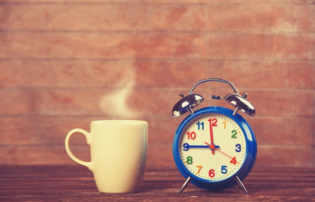 Cup of coffee and alarm clock on wooden table.