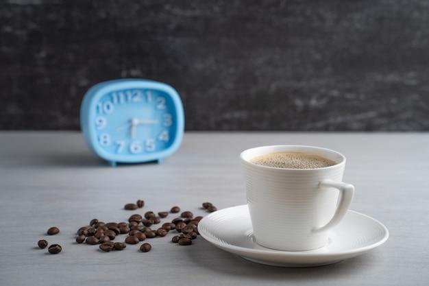 Чашка кофе и синий будильник на белом столе.
