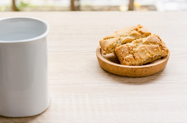 Cup of coffee and apple pine on wooden table in morning time