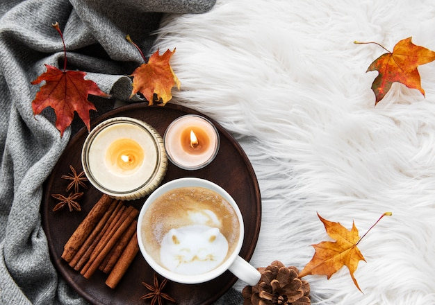Cup of coffee and autumn leaves on a fur background