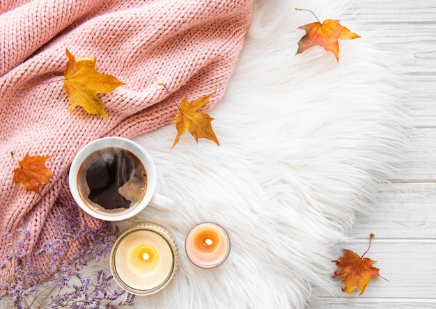 Cup of coffee and autumn leaves on a fur