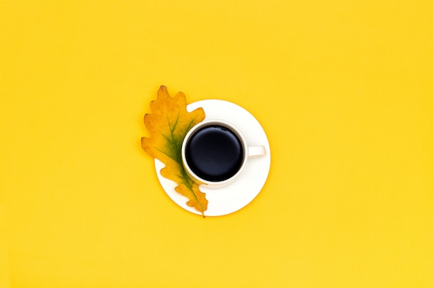 Cup of coffee and autumn oak leaf on yellow background