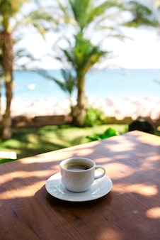 A cup of coffee on the background of the ocean.