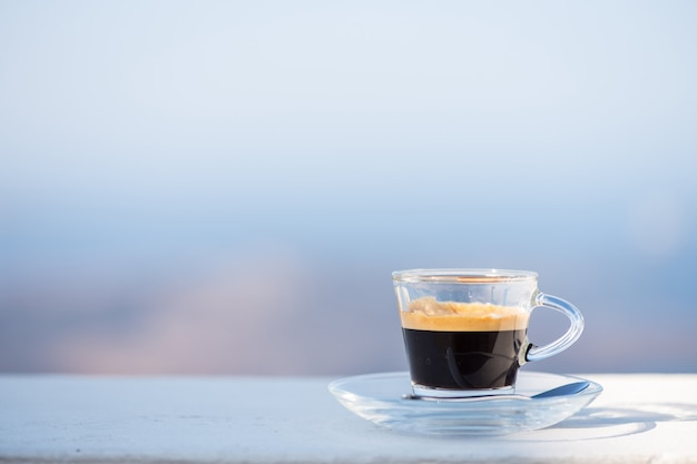 Cup of coffee on balcony with sea view.