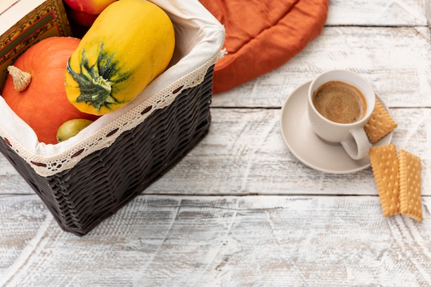 Cup of coffee next to basket with pumpkins