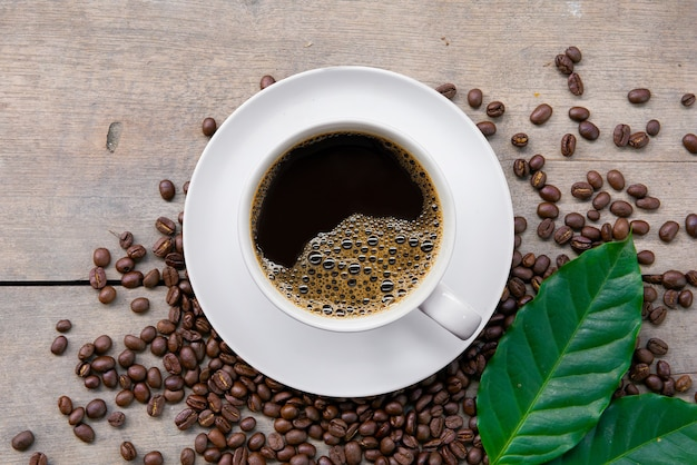 Cup of coffee and bean on black wooden table background. top view