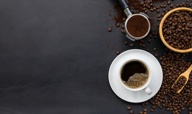 Cup of coffee and bean on black wooden table