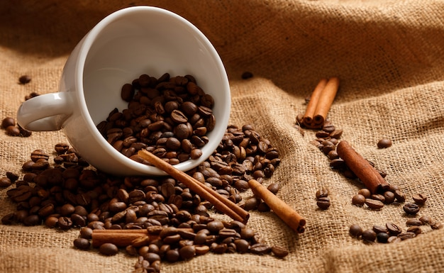 Cup, coffee beans and cinnamon sticks