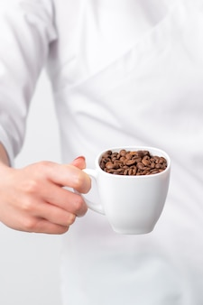 Cup of coffee beans in female hand