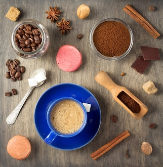 Cup of coffee and beans on wooden background, top view