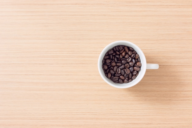 Cup and coffee beans on wooden background with copy space