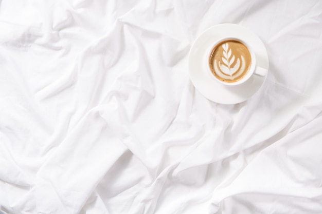 Cup of coffee in bed. morning flatlay in white bed. coffee and morning routine.