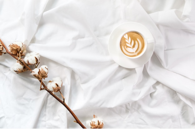 Cup of coffee in bed with cotton