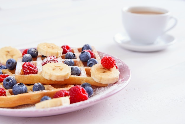 Cup of coffee and belgian waffles with blueberries, raspberries, bananas and sugar powder on white background. concept of tasty and healthy food.