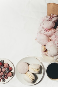 A cup of coffee berries macaroons and peony flowers on the bed
