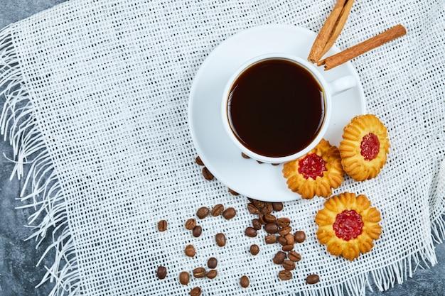 Una tazza di caffè, biscotti, chicchi di caffè e cannella.