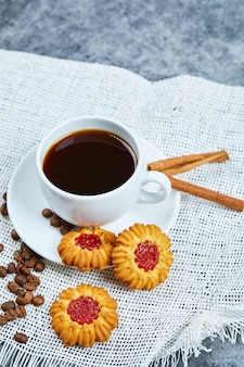 A cup of coffee, biscuits, coffee beans and cinnamon.
