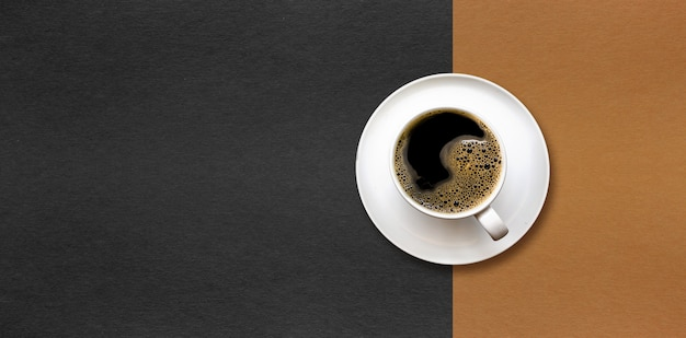 Cup of coffee on black and brown paper background.