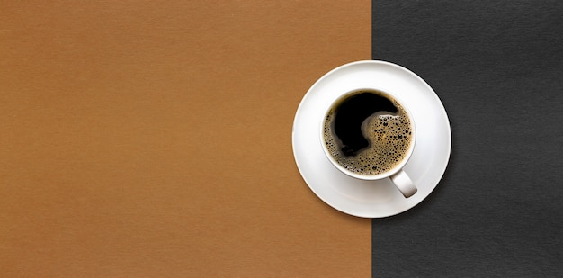 Cup of coffee on black and brown paper