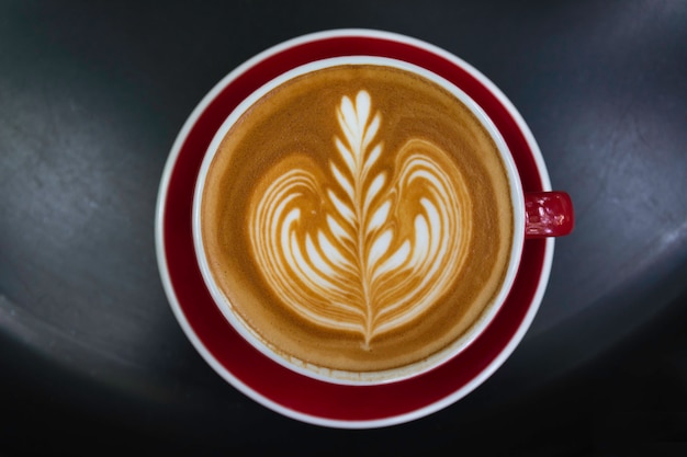 A cup of coffee on black table. top view of coffee latte art. drink and art concept.