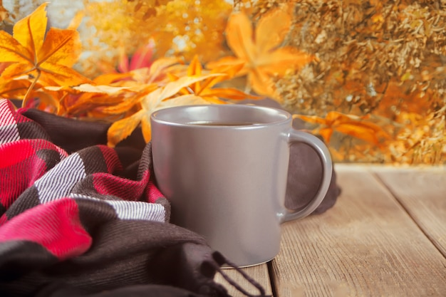 Cup of coffee, blanket and autumn leaves.
