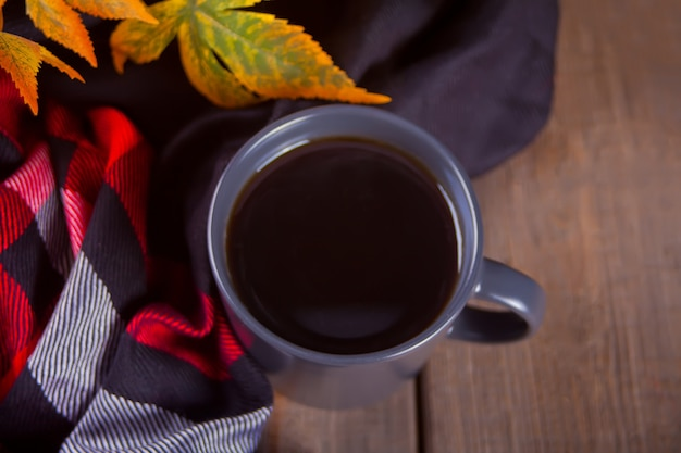 Cup of coffee, blanket and autumn leaves