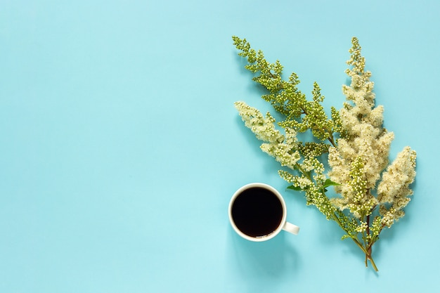 Cup of coffee and blooming twig white flowers on blue paper background