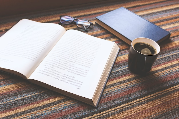 Cup of coffee and book on carpet background